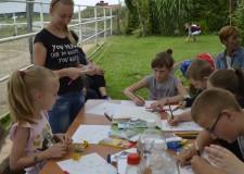 Powiększ zdjęcie Dzieci siedzą przy stole i rysują