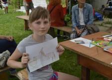 Powiększ zdjęcie Dziewczynka prezentuje wykonany przez siebie rysunek