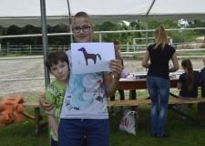 Powiększ zdjęcie Dwóch chłopców prezentuje wykonany przez siebie rysunek