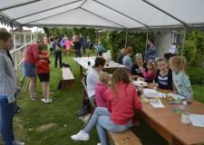 Powiększ zdjęcie Dzieci, rodzice i opiekunowie siedzą przy stołach: malują, rysują, rozmawiają