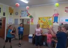 Powiększ zdjęcie dzieci stojąc w kole uczestniczą w zajęciach z muzykoterapii
