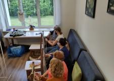 Powiększ zdjęcie pięć pań siedzi na wersalkach i zaplata przy pomocy krzeseł makramy