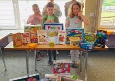 Powiększ zdjęcie dzieci stoją za stolikiem, na którym prezentują różne gry planszowe