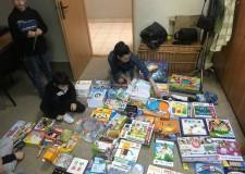 Powiększ zdjęcie Dwójka dzieci wraz z osoba dorosłą rozkłada na podłodze dużą ilość gier planszowych