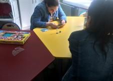 Powiększ zdjęcie dwie dziewczynki siedzą przy stoliku i grają w grę
