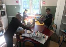 Powiększ zdjęcie czwórka dzieci z zaciekawieniem ogląda zgromadzone na stołach gry