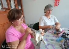 Powiększ zdjęcie Na zdjęciu dwie uczestniczki projektu siedzą przy stole i wykonują lalki
