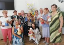 Powiększ zdjęcie Na zdjęciu stoją uczestniczki projektu i trzymają w rękach zrobione przez siebie lalki