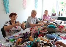 Powiększ zdjęcie Na zdjęciu trzy uczestniczki projektu siedzą przy stole i wykonują lalki