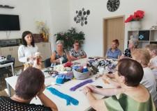 Powiększ zdjęcie Na zdjęciu uczestnicy projektu siedzą przy stole i wykonują lalki