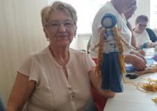 Powiększ zdjęcie Uczestniczka projektu pokazuje zrobioną przez siebie lakę w blond warkoczach, niebieskim nakryciu głowy, białej bluzeczce i niebieskiej spódnicy