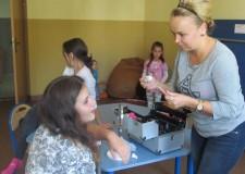 Powiększ zdjęcie Dziewczynka podczas wykonywania makijażu