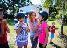 Powiększ zdjęcie trzy dziewczynki zakładają kaski przed rozpoczęciem jazdy konnej