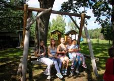 Powiększ zdjęcie dzieci huśtają się na huśtawce wraz z wychowawcą