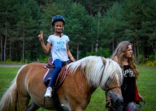 Powiększ zdjęcie dziewczynka siedzi na koniu prowadzonym przez instruktora