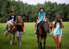 Powiększ zdjęcie dwie dziewczynki siedzą na koniach prowadzonych przez instruktorów