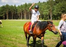 Powiększ zdjęcie chłopiec siedzi na koniu prowadzonym przez instruktora