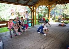 Powiększ zdjęcie dzieci patrzą jak koleżanka prezentuje figurę akrobatyczną-